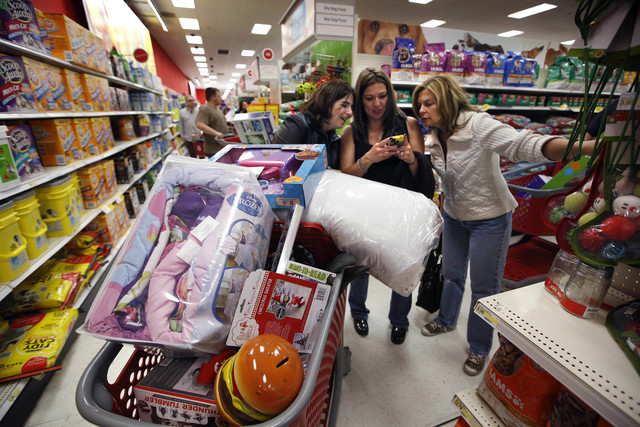 In this Nov. 28, 2014 file photo, Target shoppers Kelly Foley, left, Debbie Winslow, center, and Ann Rich use a smartphone to look at a competitor's prices while shopping  shortly after midnight o ...