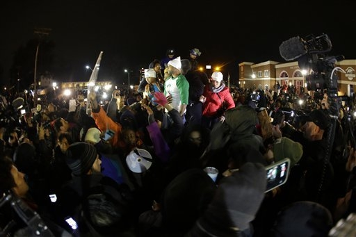 Lesley McSpadden, the mother of Michael Brown, left standing on the top of a car, reacts as she listens to the announcement of the grand jury decision Monday, Nov. 24, 2014, in Ferguson, Mo. A gra ...
