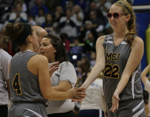 Mount St. Joseph's Lauren Hill slaps hands with Brilyn Webb, left, before the start of her first NCAA college basketball game against Hiram University at Xavier University in Cincinnati on Sunday  ...