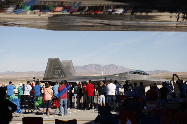 Spectator wave to the F-22 Raptor aircraft pilot after performing during the Aviation Nation air show at Nellis Air Force Base in Las Vegas Saturday, Nov. 8, 2014. (Erik Verduzco/Las Vegas Review- ...
