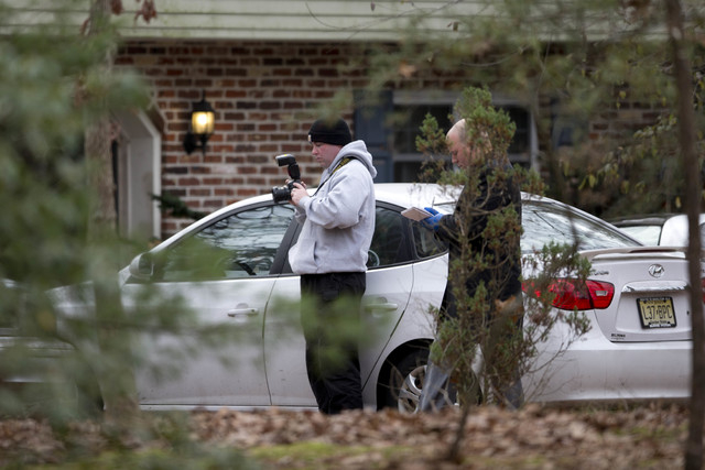 Investigators work at the scene of a shooting Thursday, Nov. 20, 2014, in Tabernacle, N.J. New Jersey State Police say two people are dead and two were found wounded in a shooting in the southern  ...