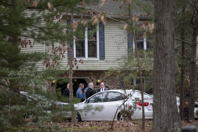 Members of law enforcement gather at the scene of a shooting Thursday, Nov. 20, 2014, in Tabernacle, N.J. New Jersey State Police say two people are dead and two were found wounded in a shooting a ...