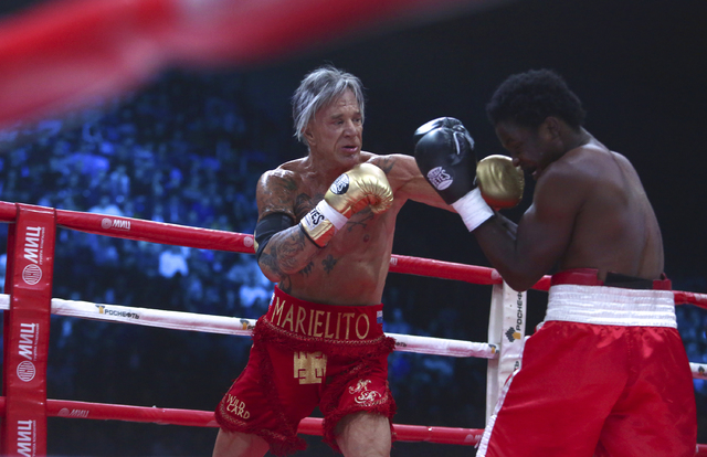 Mickey Rourke, left, punches his opponent, Elliot Seymour of the United States, during their professional boxing match at the Luzhniki Stadium in Moscow on Friday, Nov. 28, 2014. The Hollywood act ...