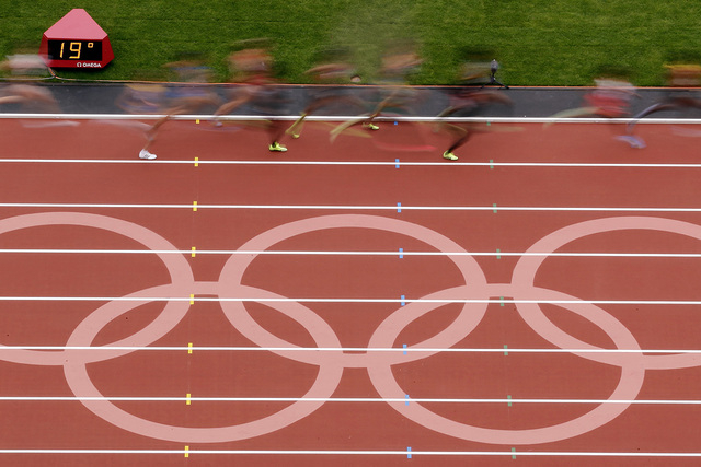 Runners make their way past a logo on the track during a women's 5000-meter heat at athletics in the Olympic Stadium at the 2012 Summer Olympics, London, Tuesday, Aug. 7, 2012. (AP Photo/Morry Gash)