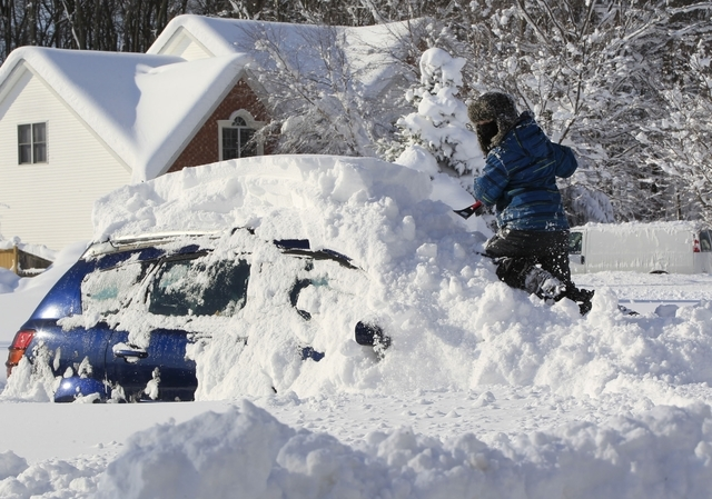 Braeden Attig,11, removes snow from a buried car along Powers Road in Orchard Park, N.Y. on Wednesday, Nov. 19, 2014.  A ferocious lake-effect storm left the Buffalo area buried under 6 feet of sn ...