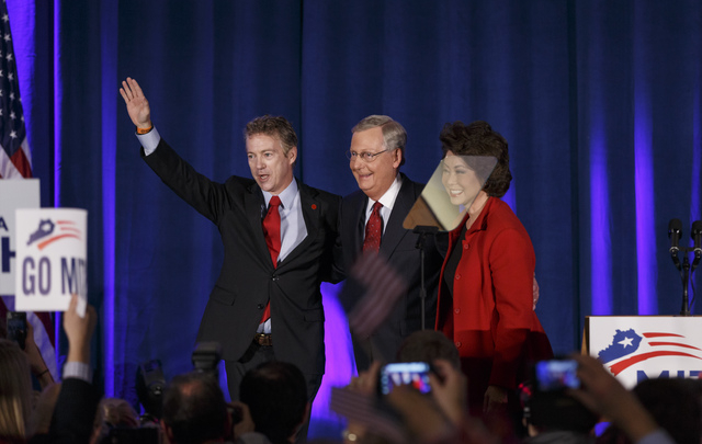 Senate Minority Leader Mitch McConnell of Ky., center, celebrates with Sen. Rand Paul, R-Ky., left, and his wife, former Labor Secretary Elaine Chao, at an election night party in Louisville, Ky., ...