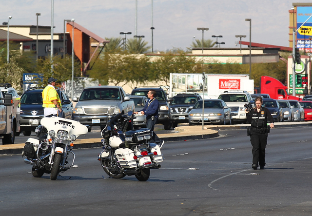 Las Vegas police investigate the scene where a vehicle hit and killed a 63-year-old male pedestrian and injured an 18-month-old child on South Rainbow Boulevard near Warm Springs Road in Las Vegas ...