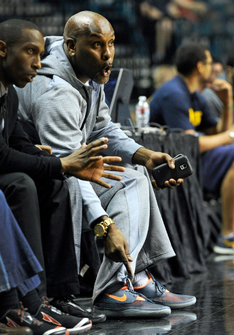 Former NBA player Gary Payton gestures as he watches his son, Gary Payton II, play from court side during the MGM Grand Main Event at the MGM Grand Garden Arena on Monday, Nov. 24, 2014, in Las Ve ...
