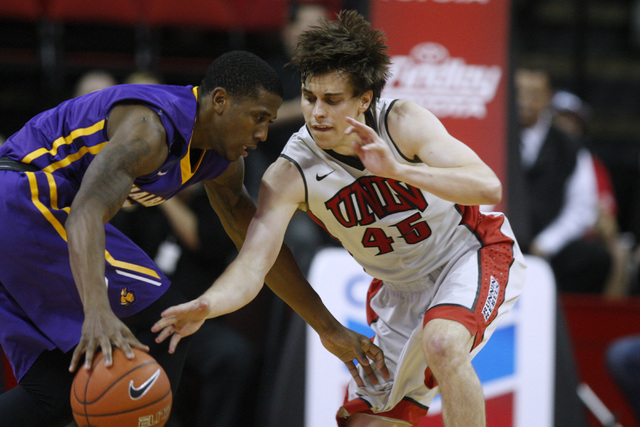 UNLV guard Cody Doolin tries to knock the ball away from Albany guard Evan Singletary during their game Saturday, Nov. 29, 2014 at the Thomas & Mack Center. (Sam Morris/Las Vegas Review-Journal)