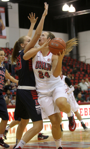 UNLV womenճ basketball senior forward Alana Cesarz (24) drives past Dixie State center Taylor Mann in the second half of an exhibition game at the Cox Pavilion Monday, Nov. 10, 2014. (K.M. C ...