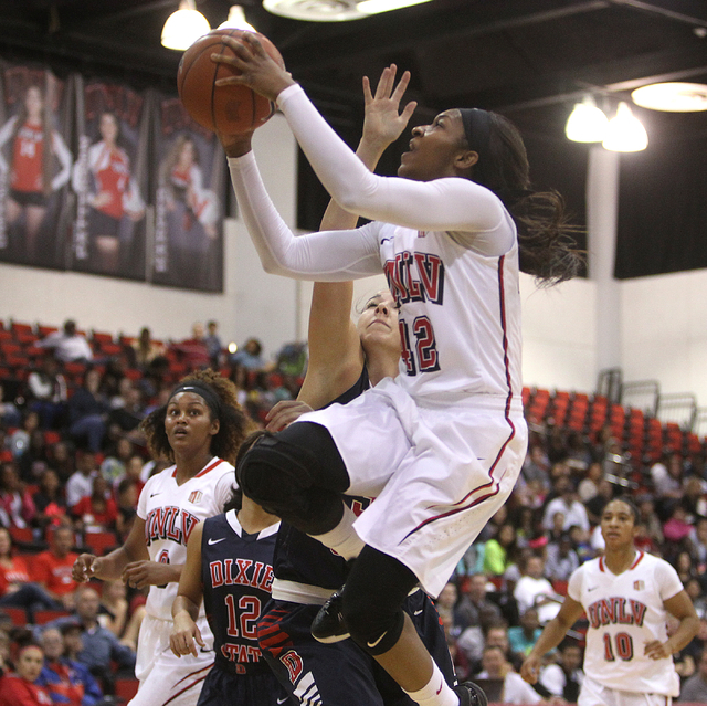UNLV womenճ basketball senior guard Danielle Miller (42) goes up for a shot past Dixie State center Haileigh Emerine  in the first half of an exhibition game at the Cox Pavilion Monday, Nov. ...