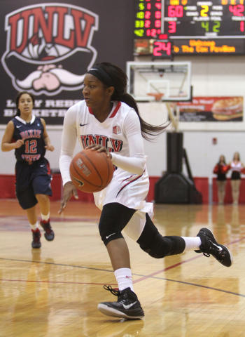 UNLV womenճ basketball senior guard Danielle Miller (42) drives past Dixie State guard Leslie Tademy in the second half of an exhibition game at the Cox Pavilion Monday, Nov. 10, 2014. (K.M. ...