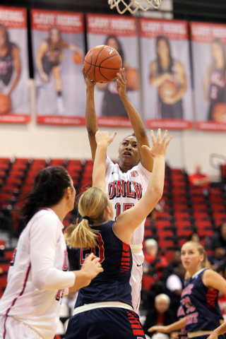 UNLV womenճ basketball sophomore forward Diamond Major shoos over Dixie State forward Ashlee Burge (20) in the first half of an exhibition game at the Cox Pavilion Monday, Nov. 10, 2014. (K. ...