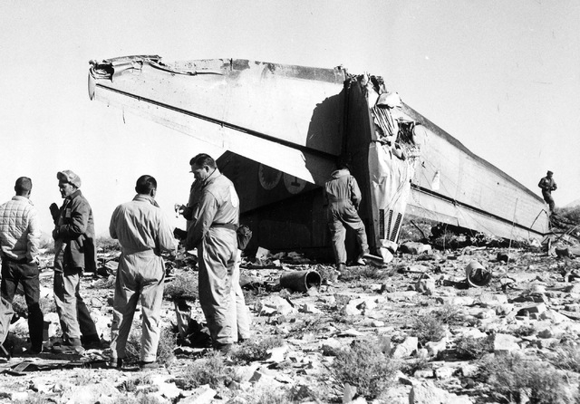 Investigators gather near the tail section of Bonanza Air Lines Flight 114, which crashed into a mountain just south of Las Vegas on Nov. 15, 1964, killing all 29 people on board. (Courtesy of Scr ...