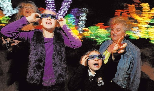 Sienna Tobler, 10, left, and Katie Kriey, 7, use 3-D glasses to admire the lights as Mary Ann O'Reilly looks on during the annual Holiday Cactus Lighting at the Ethel M Chocolates Cactus Garden, ...