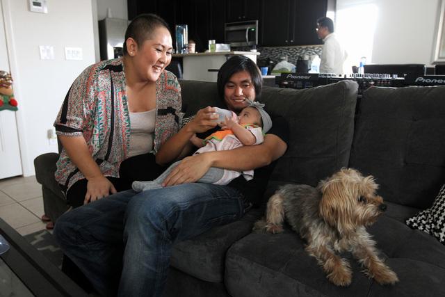 Nina Santos watches as her husband, Francis Santos, feeds their daughter Olivia Santos Wednesday, Nov. 19, 2014.  (Sam Morris/Las Vegas Review-Journal)