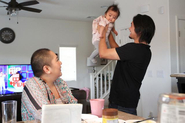 Nina Santos watches as her husband, Francis Santos, plays with their daughter Olivia Santos Wednesday, Nov. 19, 2014.  (Sam Morris/Las Vegas Review-Journal)