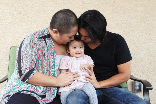 Nina and Francis Santos give a kiss to their daughter Olivia Santos Wednesday, Nov. 19, 2014.  (Sam Morris/Las Vegas Review-Journal)