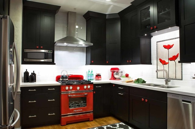 Jill Buckner Photography A 14-by-12 foot Atlanta kitchen designed by Kandrac & Kole Interior Designs features black cabinets with red hand-blown glass knobs, a retro red stove from Big Chill and a ...