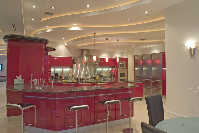 """Courtesy photo The """"rosso corsa"""" (racing red in Italian) gourmet kitchen off the 1,760-foot family room gives the house a boost of color. Pininfarina, the same Italian firm that designs spaces ..."""