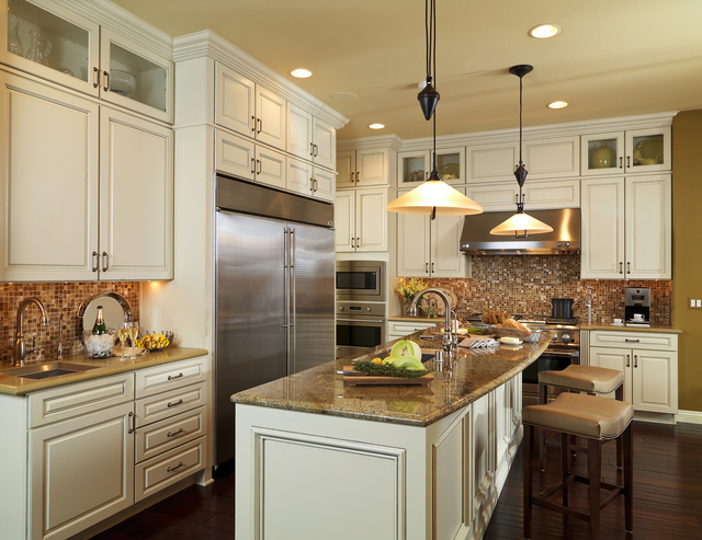 Courtesy photo Full height (10') cabinetry with custom putty glaze over cream finish, punctuated by seeded glass upper cabinet doors.  Mosaic backsplash from Oceanside Tile procured through the La ...