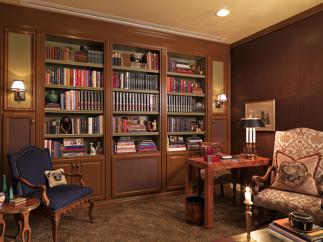 """Courtesy photo Custom millwork/bookcases house a collection of books, photographs and travel """"finds"""".  The walls are upholstered in a rich, chocolate faux leather and a leopard patterned carpet ad ..."""