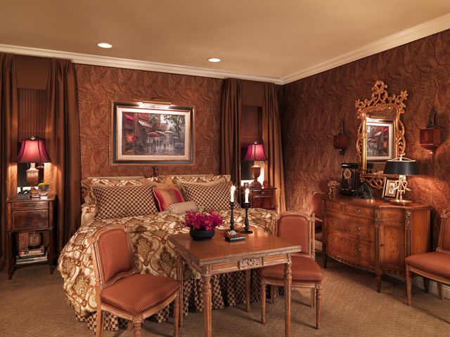 Courtesy photo A posh master bedroom setting is achieved with upholstered walls done in an autumnal paisley and a mix of continental antique furnishings to create a soothing retreat.