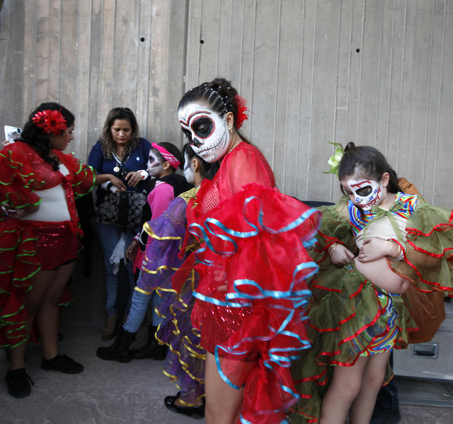 Alexandra Rodriguez, 13, center, Madison Benway, second from right, 9, and Michael Benway, 7, get ready to perform on stage at the Springs Preserve for the Dia de los Muertos celebration in Las Ve ...