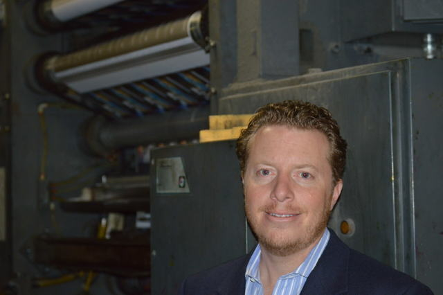 Allan Creel Jr., president of Creel Printing, stands in front of one of many presses at Creel Printing.