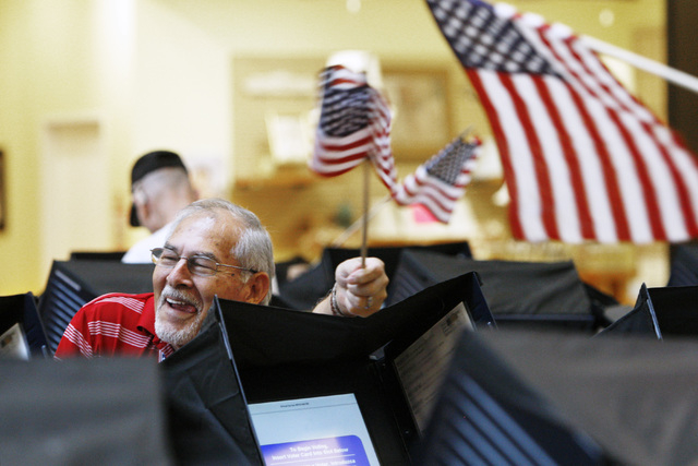 Poll worker Jesse Cano smiles and waves a flag to direct a voter to an idle voting booth during early voting at the Galleria Mall in Henderson Saturday, Oct. 18, 2014.  (Sam Morris/Las Vegas Revie ...