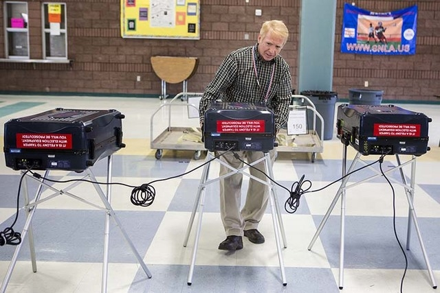 Clark County Public Works employee Michael Dunning sets up voting machines in the cafeteria at Lied Middle School on Monday, Nov. 3,2014. A low turn out is expected in Tuesday midterm election. (J ...