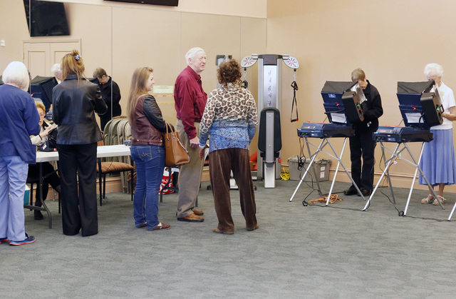 Juana Leia Jordan, center, a Clark County Election Election Department's worker, talks to voters as they wait in line to cast their vote Tuesday, Nov. 4, 2014, at Las Ventanas Community Center, 10 ...