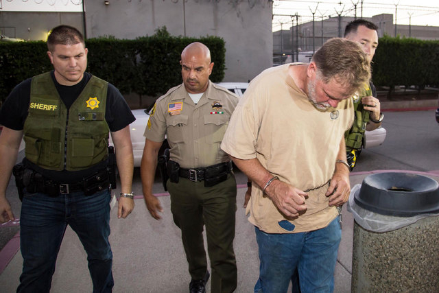 Investigators from the San Bernardino County Sheriff's Department homicide unit take Charles Merritt into custody Wednesday, Nov. 5, 2014, for the murders of Joseph, Summer, Gianni and Joseph M. ...