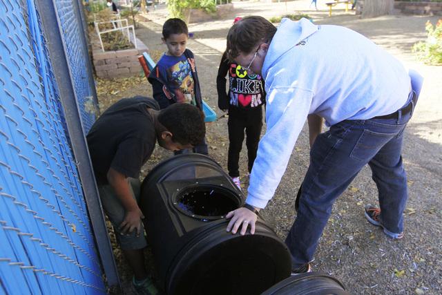 Nick Demott, a third-grade teacher at Walter Bracken STEAM Academy, checks a compost bin with his students. (Sam Morris/View)
