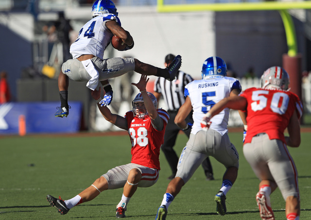 Air Force running back Jon Lee (24) leaps over UNLV place kicker Jonathan Leiva (38) on a kick return during the first half of their Mountain West Conference game Saturday, Nov. 8, 2014 at Sam Boy ...