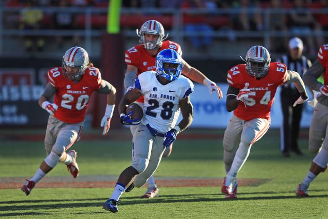 Air Force running back Jacobi Owens (28) gets away from UNLV defensive back Matt Vinal (20), UNLV defensive lineman Dominic Baldwin (97) and UNLV linebacker Iggy Porchia (54) for a 55-yard run to  ...