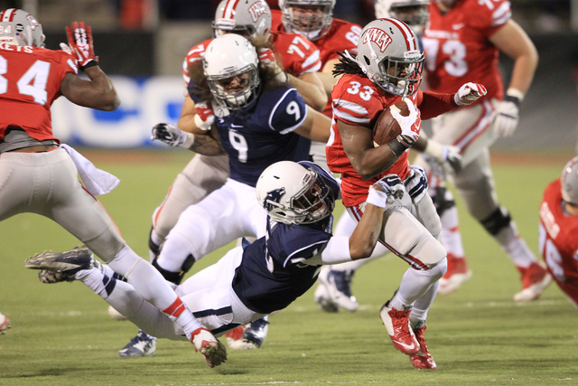UNLV running back Shaquille Murray-Lawrence is brought down by Nevada defensive back Kendall Johnson during their game Saturday, Nov. 29, 2014 at Sam Boyd Stadium. (Sam Morris/Las Vegas Review-Jou ...