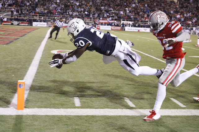 Nevada running back James Butler leaps towards the end zone after stepping out of bounds while being pursued by UNLV defensive back Mike Horsey during their game Saturday, Nov. 29, 2014 at Sam Boy ...