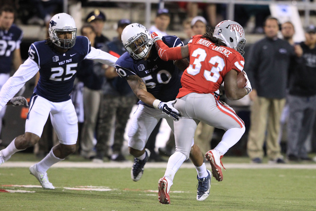 UNLV running back Shaquille Murray-Lawrence pushes off Nevada linebacker Jonathan McNeal during their game Saturday, Nov. 29, 2014 at Sam Boyd Stadium. Nevada won 49-27. (Sam Morris/Las Vegas Revi ...