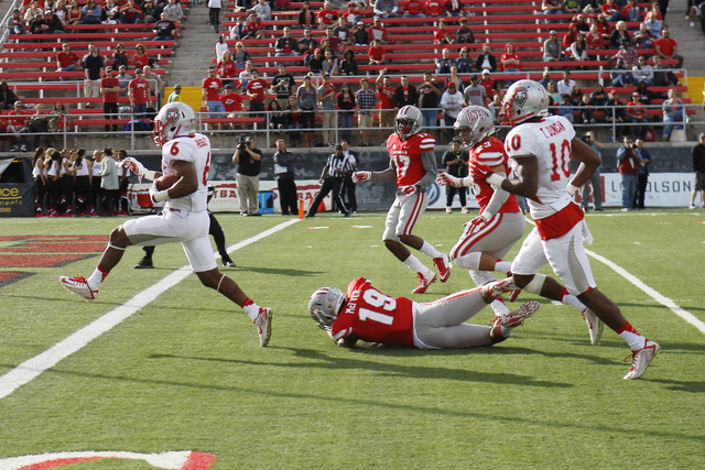 New Mexico Lobos running back Jhurell Pressley (6) gets past UNLV Rebels defensive back Torry McTyer (19) and into the end zone during their Mountain West Conference game Saturday, Nov. 1, 2014 at ...