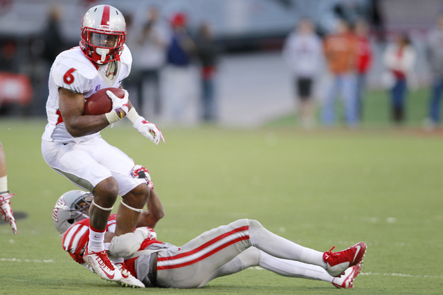 New Mexico Lobos running back Jhurell Pressley (6) is tackled by UNLV Rebels defensive back Mike Horsey (32) during their Mountain West Conference game Saturday, Nov. 1, 2014 at Sam Boyd Stadium.  ...