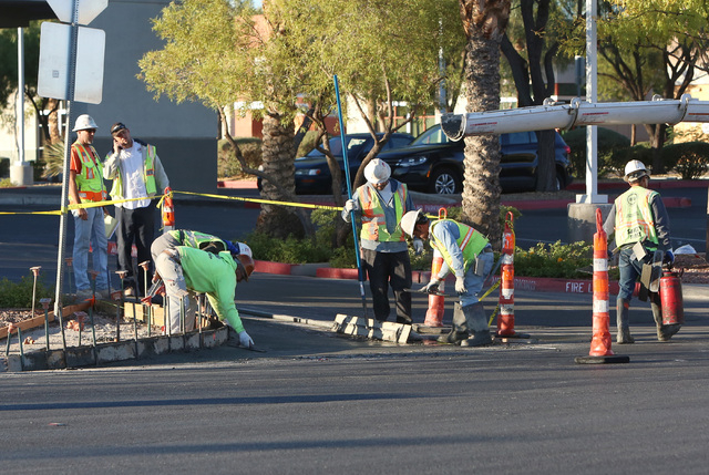 Concrete workers work on the sidewalk on Warm Springs Road, near Arroyo Grande Boulevard, Friday, Nov. 7, 2014, in Henderson. A road construction flag person is in serious condition after she was  ...