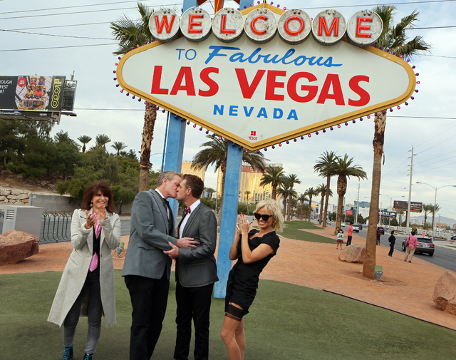 Dan Mathews, center left, senior vice president of PETA, and his partner Jack Ryan, center right, kiss during their Thanksgiving Day wedding ceremony at the Welcome to Las Vegas sign Thursday. Roc ...