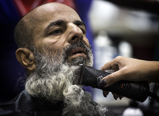 Mahesh Kumar gets his beard trimmed during the annual Project Homeless Connect at Cashman Center, 850 Las Vegas Boulevard North, on Wednesday, November 19,2014. Thousands of people attended the an ...