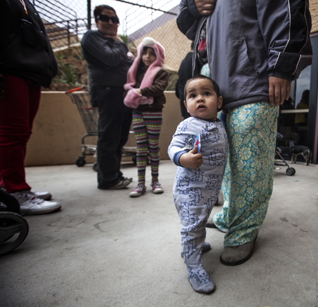 Francisco Gutierrez,center, turning 1-year-old on Saturday, holds his mother's Daniela Gutierrez leg while standing in line at  the annual Project Homeless Connect at Cashman Center, 850 Las Vegas ...