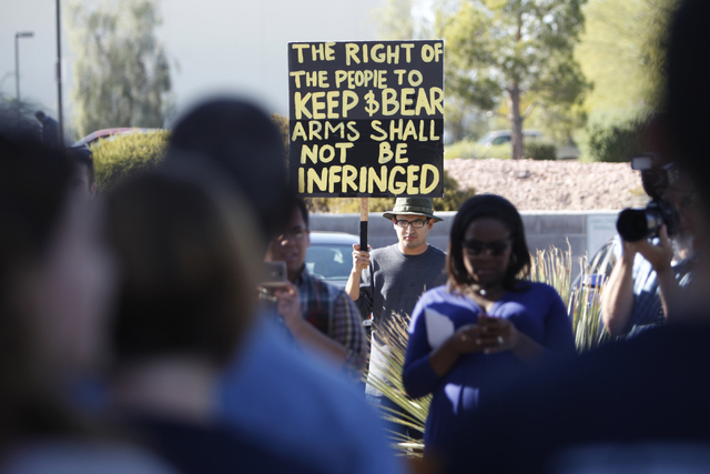 Andrew Flores protests outside of the Clark County Election Center in North Las Vegas where volunteers with Nevadans for Background Checks hosted a press conference before submitting 246,674 signa ...
