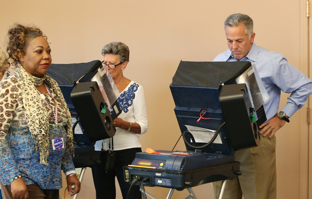Clark County sheriff candidate Joe Lombardo, right, casts his vote as Juana Leia Jordan, left, an election poll worker, looks on  Tuesday, Nov. 4, 2014, at Las Ventanas Community Center, 10401 W.  ...