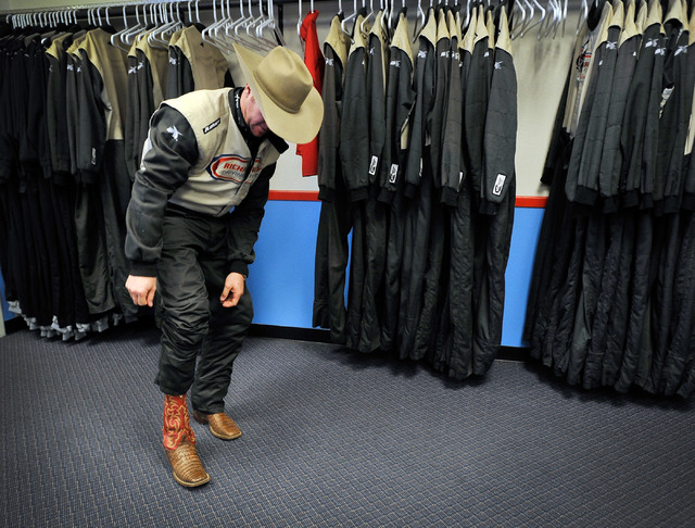 Rodeo champion Trevor Brazile slips on his cowboy boots back on after donning a driver fire suit before he takes to the track at the Las Vegas Motor Speedway on Sunday, Nov. 30, 2014. Brazile and  ...