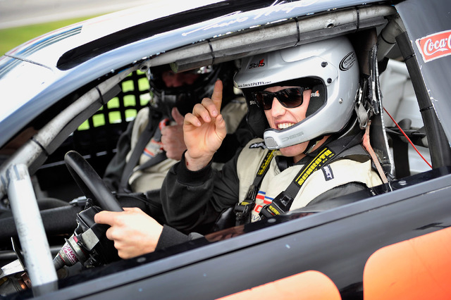 Rodeo champion Tuff Cooper signals as he sits in the drives seat of a race car at the Richard Petty Driving Experience at the Las Vegas Motor Speedway on Sunday, Nov. 30, 2014. Cooper and fellow c ...