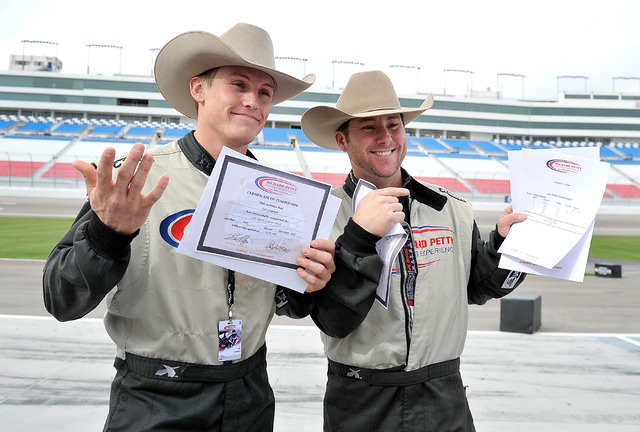 Rodeo champions Tuff Cooper, left, and Trevor Brazile pose with their results after the two raced at the Richard Petty Driving Experience at the Las Vegas Motor Speedway on Sunday, Nov. 30, 2014.  ...